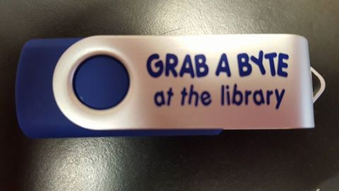 Blue and White Flash Drive with Words Grab a Byte at the Library on It