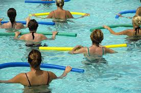 Women Performing Exercises with Noodles in Pool